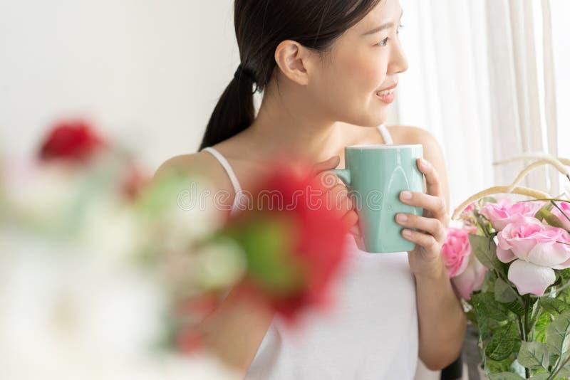Mujer asiática del retrato que se relaja con café en casa imagenes de archivo