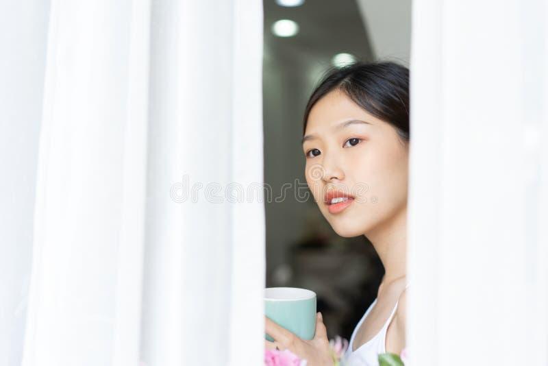 Mujer asiática del retrato que se relaja con café en casa foto de archivo