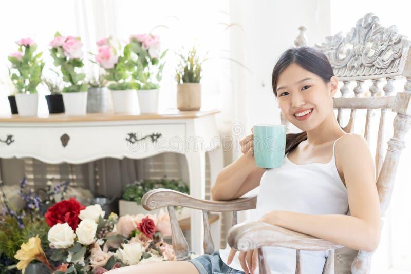 Mujer asiática del retrato que se relaja en silla de madera con café en casa fotos de archivo libres de regalías