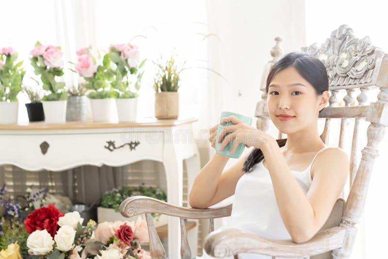 Mujer asiática del retrato que se relaja en silla de madera con café en casa imagen de archivo libre de regalías