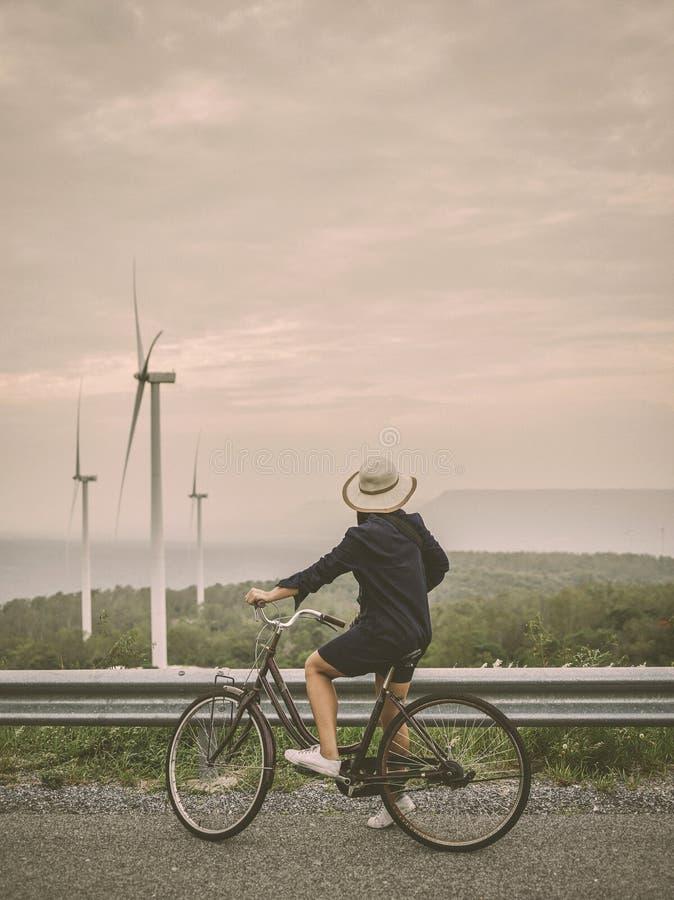 Mujer asi?tica del viajero en vestido de la mezclilla con el camino cl?sico de la bicicleta en estilo contempor?neo retro foto de archivo