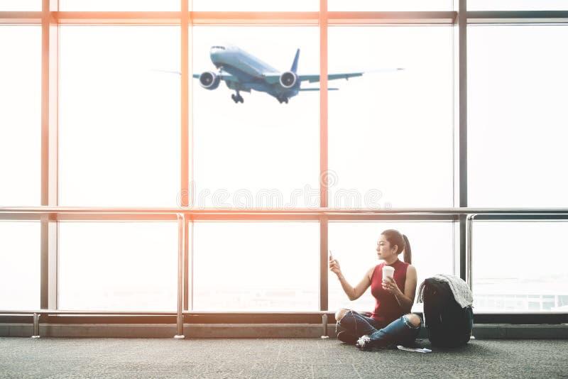 Mujer asiática del viajero que usa el teléfono elegante y bebiendo el café en el aeropuerto para el viaje en verano del día de fi imagen de archivo