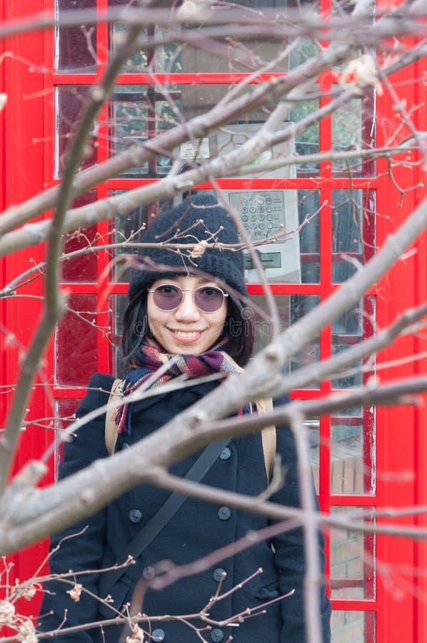 Mujer asiática delante de la cabina de teléfonos imagen de archivo