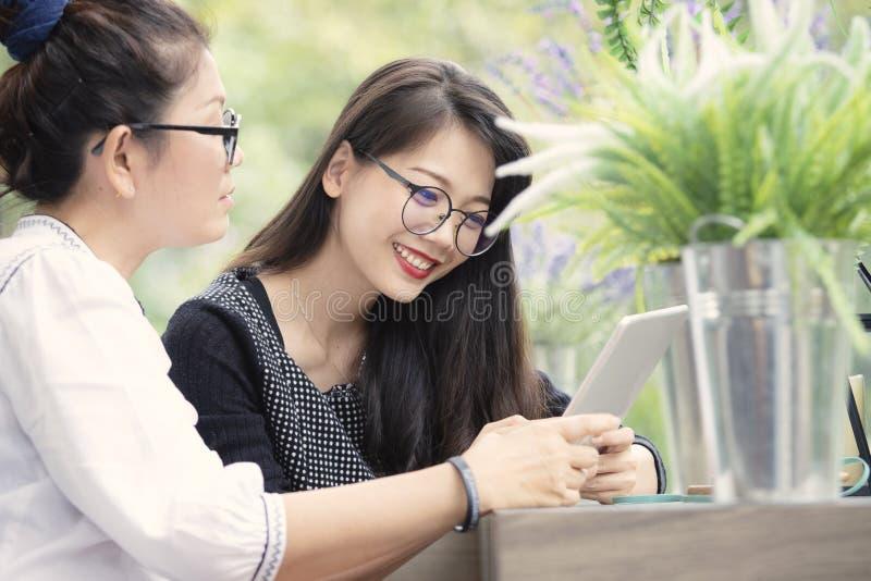 Mujer asiática dos con el teléfono elegante a disposición que habla en la sala de estar casera con la cara de la felicidad imágenes de archivo libres de regalías