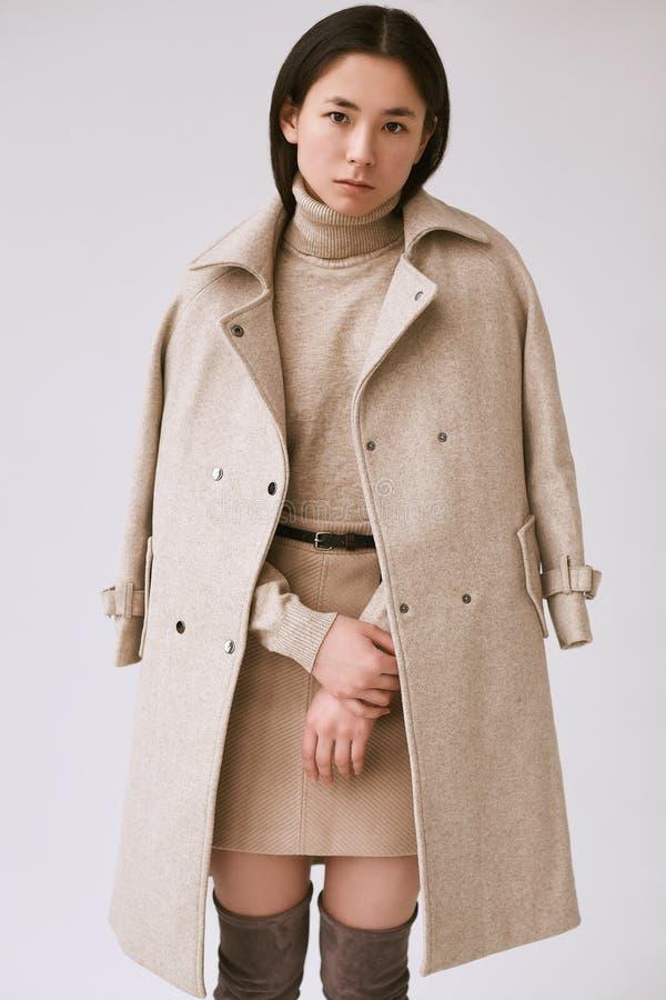Mujer asiática elegante en capa de lana de moda y falda clásica imagen de archivo