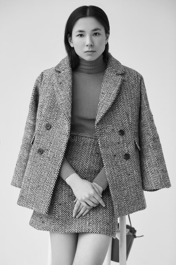 Mujer asiática elegante en capa de lana de moda y falda clásica fotografía de archivo libre de regalías