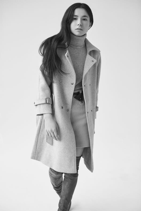 Mujer asiática elegante en capa de lana de moda y falda clásica fotos de archivo libres de regalías