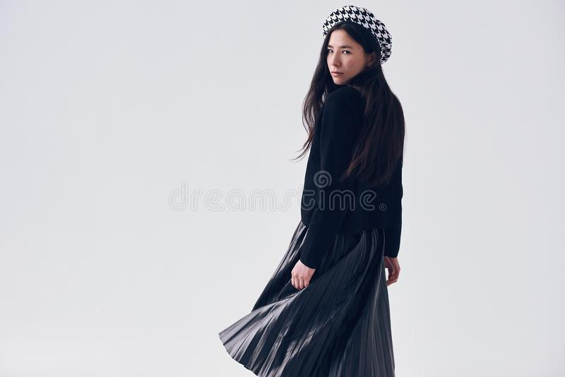 Mujer asiática elegante en falda y boina negras de moda imagen de archivo libre de regalías