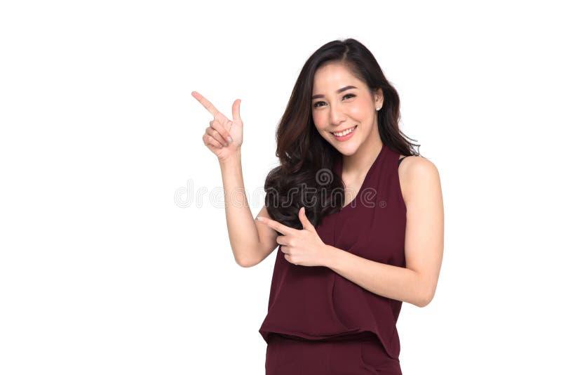 Mujer asiática elegante joven que sonríe y que señala para vaciar el espacio de la copia aislado fotos de archivo