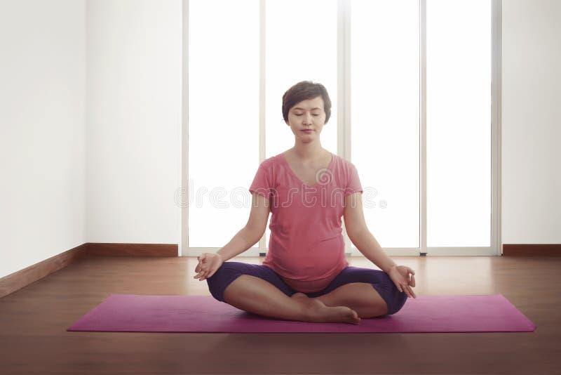 Mujer asiática embarazada que ejercita en la estera rosada foto de archivo libre de regalías