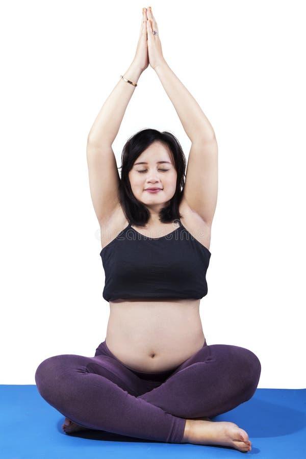 Mujer asiática embarazada que hace yoga imagen de archivo libre de regalías