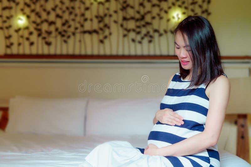 Mujer asiática embarazada que lleva una camisa rayada, imagen de archivo libre de regalías