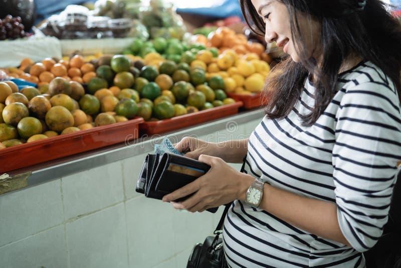 Mujer asiática embarazada sacar el dinero de su cartera para pagar mercancías imagen de archivo