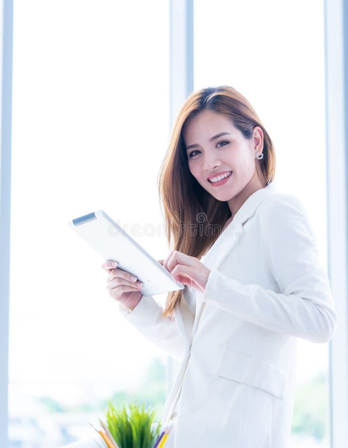 Mujer asiática en blanco usando la tableta en espacio de oficina imagen de archivo