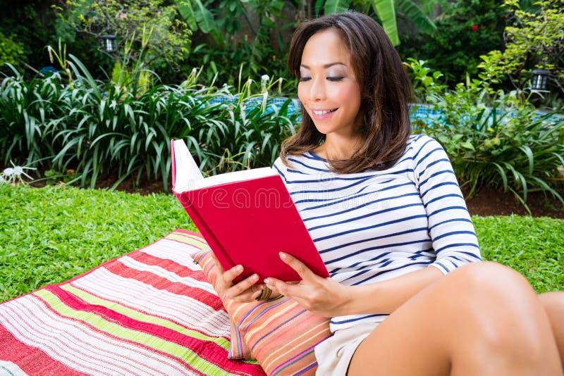 Mujer asiática en casa en libro de lectura del jardín fotografía de archivo libre de regalías