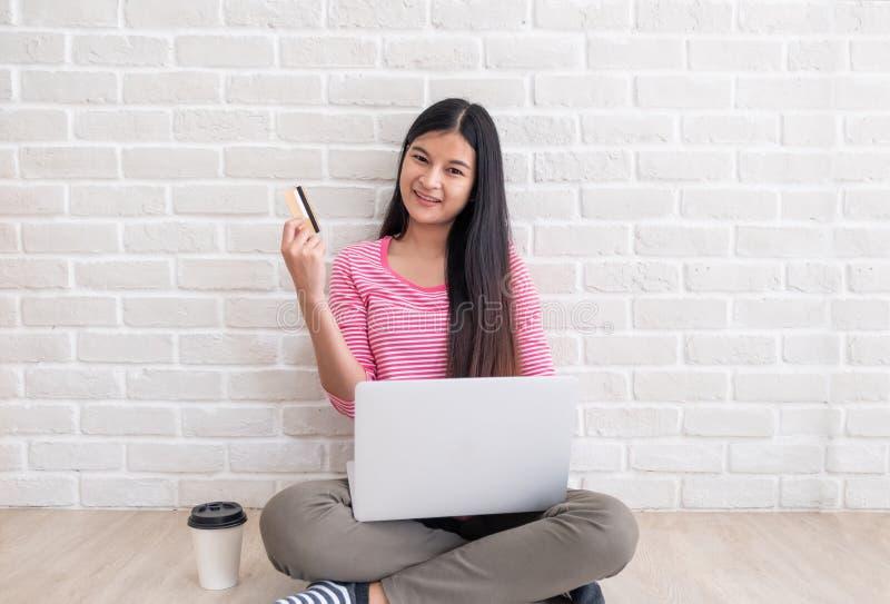 Mujer asiática en el paño casual rosado que celebra mirada de la tarjeta de crédito en la cámara y que usa el ordenador portátil  fotos de archivo libres de regalías