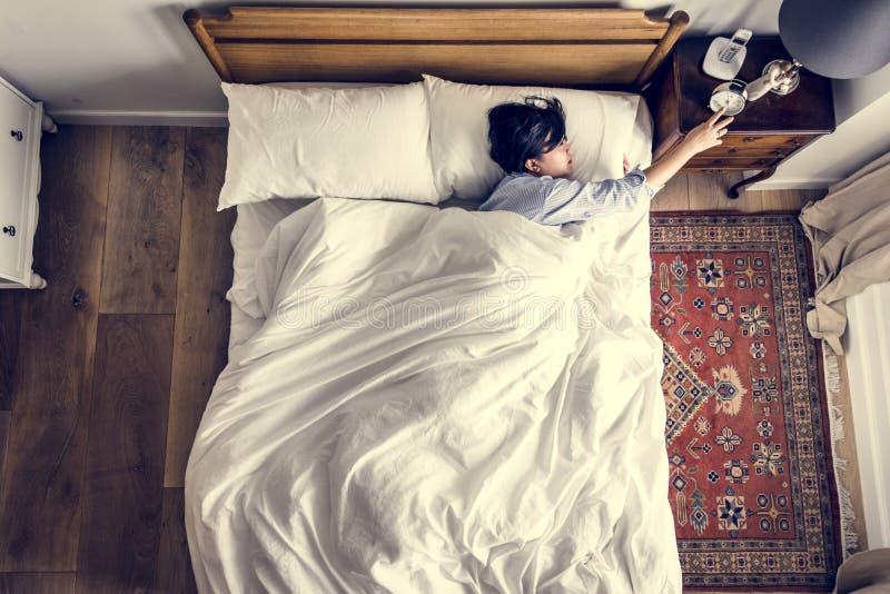 Mujer asiática en la cama que despierta por el despertador imágenes de archivo libres de regalías