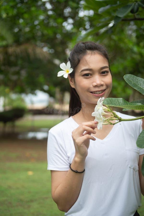 Mujer asiática en la camiseta blanca con el plumeria en su pelo, gir hermoso imagen de archivo