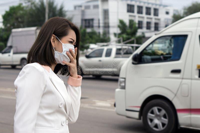 Mujer asiática en la máscara protectora que se siente mal en la calle en la ciudad con la contaminación atmosférica , El pelo cor foto de archivo libre de regalías