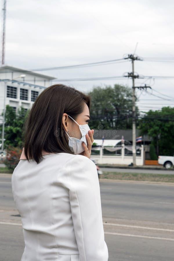 Mujer asiática en la máscara protectora que se siente mal en la calle en la ciudad con la contaminación atmosférica , El pelo cor foto de archivo