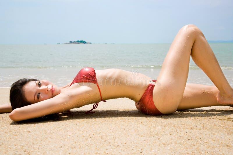 Mujer asiática en magro del bikiní en la playa del verano imagenes de archivo