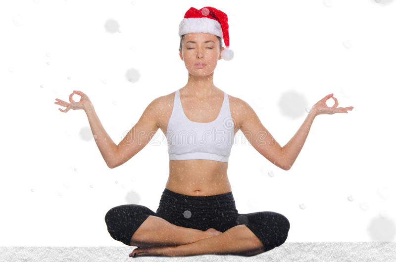 Mujer asiática en sombrero de la Navidad con yoga practicante de la nieve fotografía de archivo libre de regalías