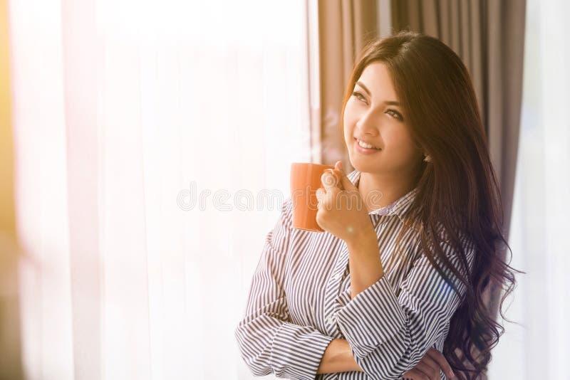 Mujer asiática en su sala de estar que bebe sosteniendo una taza del té del café imagen de archivo