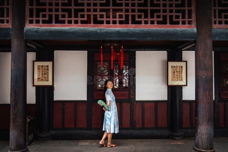 Mujer asiática en un templo que sostiene una fan de la mano foto de archivo libre de regalías