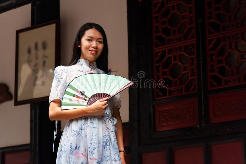 Mujer asiática en un templo que sostiene una fan de la mano fotos de archivo