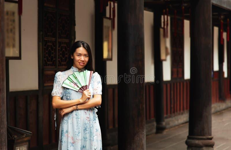 Mujer asiática en un templo que sostiene una fan de la mano foto de archivo