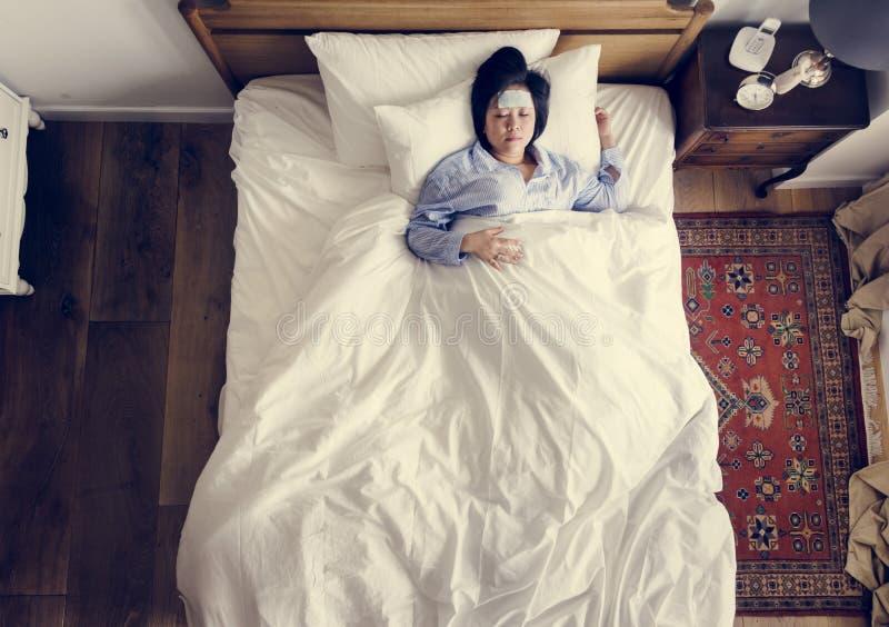 Mujer asiática enferma con fiebre que duerme en la cama imagen de archivo