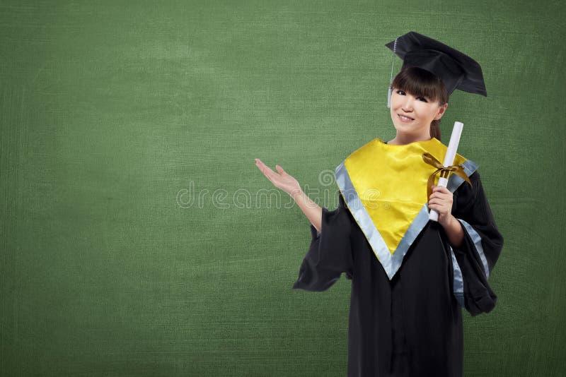 Mujer asiática feliz con el casquillo de la graduación y certificado que muestra el co imagen de archivo libre de regalías
