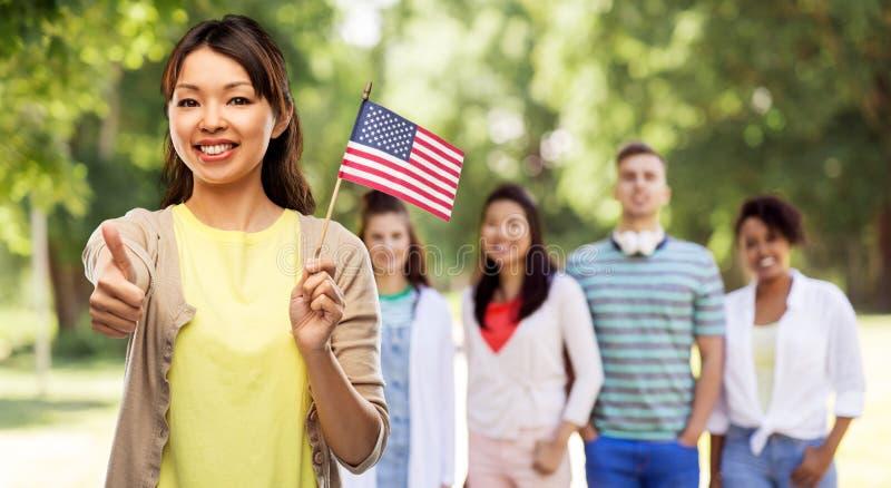 Mujer asiática feliz con la bandera americana imagen de archivo libre de regalías