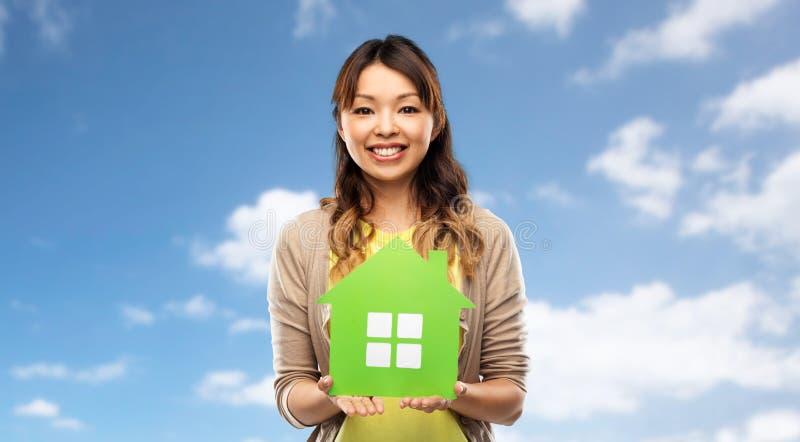 Mujer asiática feliz con la casa verde imagen de archivo libre de regalías