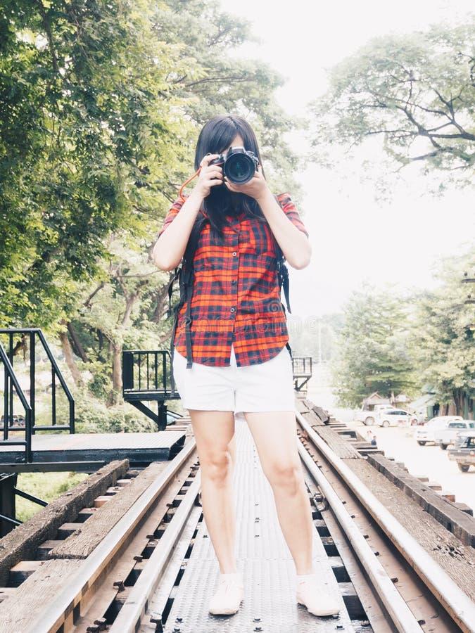 Mujer asiática feliz el vacaciones que fotografía con una cámara del dslr imagen de archivo libre de regalías