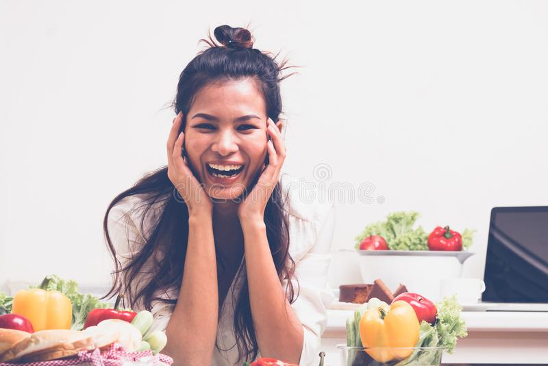 Mujer asiática feliz en cocina imagen de archivo libre de regalías