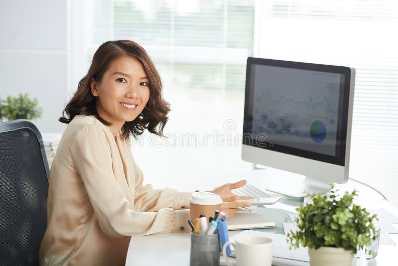 Mujer asiática feliz en la oficina imagenes de archivo