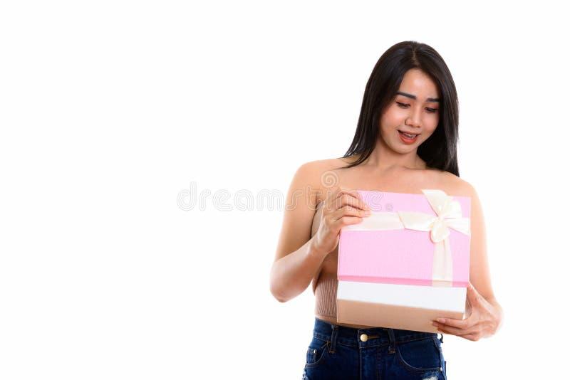 Mujer asiática feliz joven del transexual que sonríe mientras que abre el regalo b fotografía de archivo libre de regalías