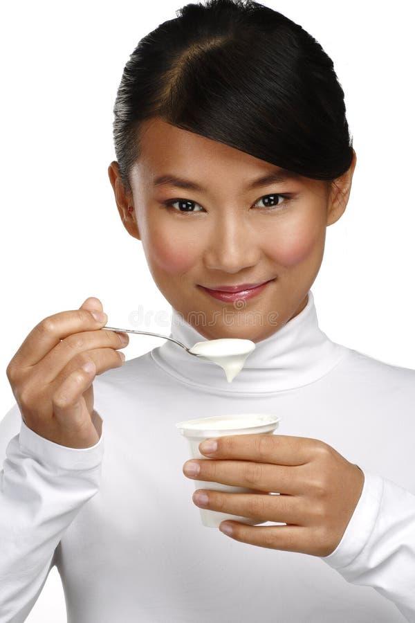 Mujer asiática feliz joven que come el yogur fresco fotos de archivo libres de regalías