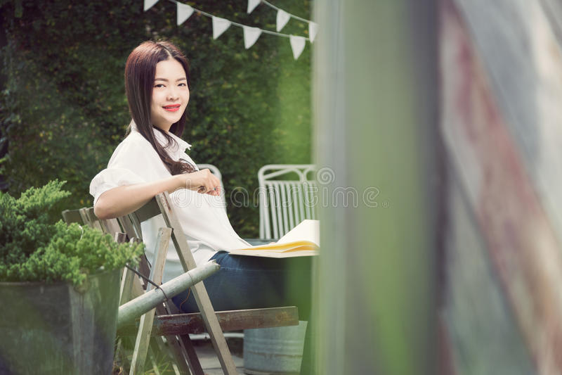 Mujer asiática feliz joven que sonríe en la cámara que sostiene un libro imagen de archivo