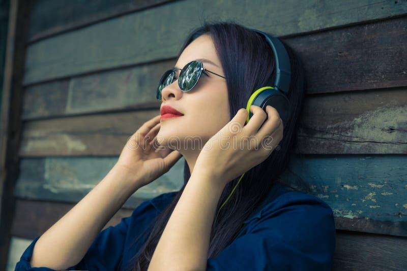 Mujer asiática feliz joven que usa el auricular para escuchar su música imagenes de archivo