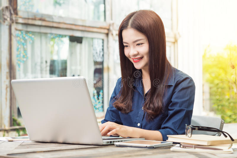 Mujer asiática feliz joven sonriente que usa tecnología en su ordenador portátil c fotos de archivo libres de regalías