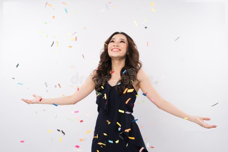 Mujer asiática feliz que celebra con confeti en el fondo blanco foto de archivo
