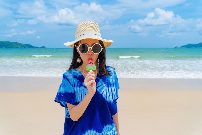 Mujer asiática feliz que come el helado de la sandía en la playa durante vacaciones de los días de fiesta del viaje al aire libre imagen de archivo libre de regalías