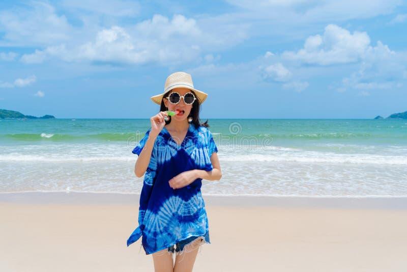 Mujer asiática feliz que come el helado de la sandía en la playa durante vacaciones de los días de fiesta del viaje al aire libre fotografía de archivo