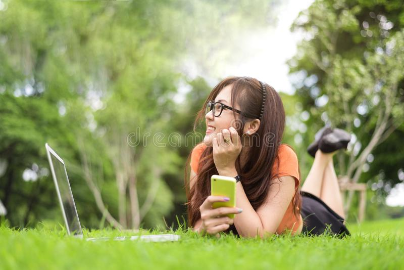 Mujer asiática feliz que descansa y que mira por otra parte en parque con smartphone Gente y concepto de las formas de vida Tema  imágenes de archivo libres de regalías