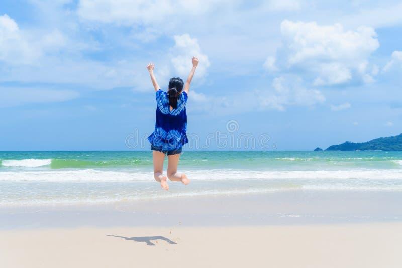 Mujer asiática feliz que salta, relajándose y gozando en la playa durante vacaciones de los días de fiesta del viaje al aire libr fotos de archivo
