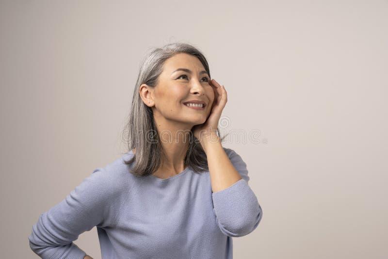 Mujer asiática feliz que sonríe en el fondo blanco imagen de archivo libre de regalías