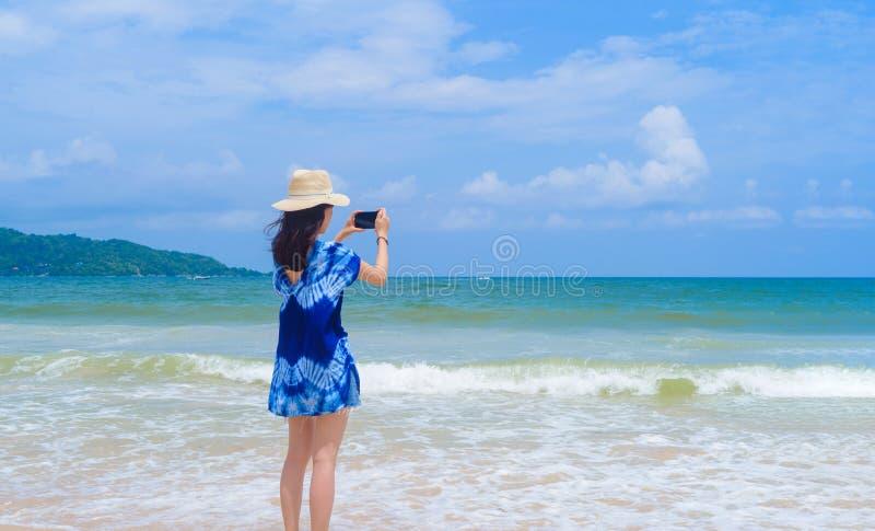 Mujer asiática feliz que usa el teléfono móvil para tomar una foto por la cámara en medios sociales en la playa durante vacacione foto de archivo