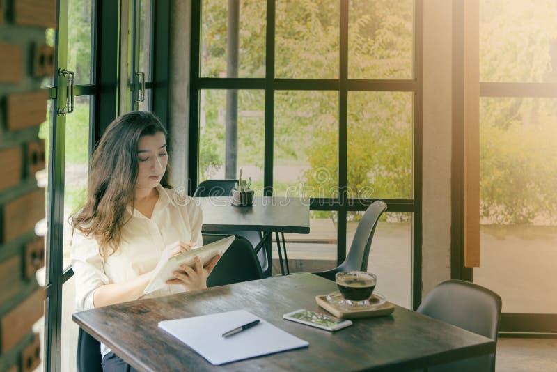 Mujer asiática feliz que usa la tableta en cafetería con tono del vintage Comercio electrónico, educación de la universidad, tecn foto de archivo libre de regalías